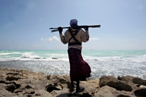 (FILES) -- A file photo taken on January 7, 2010 shows an armed Somali pirate along the coastline while the Greek cargo ship, MV Filitsa, is seen anchored just off the shores of Hobyo, northeastern Somalia, where its being held by pirates. On the 20th anniversary of president Mohamed Siad Barre's ouster that triggered Somalia's descent into chaos and one of Africa's longest civil wars, prospects for peace remain slim, analysts said. The Horn of Africa country is now best known to the outside world for being the place that inspired the Hollywood war movie